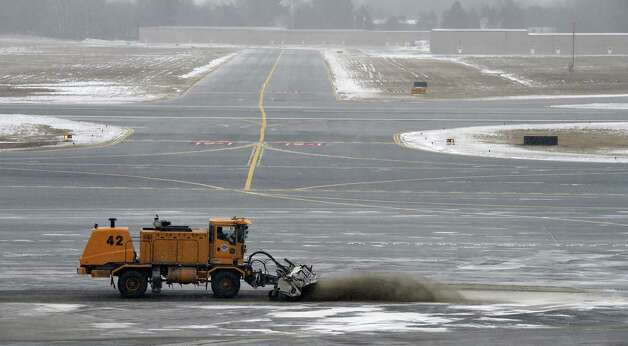 As the snow started to fall a maintenance crew uses a large broom to remove leftover sand Tuesday morning Jan. 27, 2015 at the Albany International Airport in Colonie, N.Y.        (Skip Dickstein/Times Union) Photo: SKIP DICKSTEIN