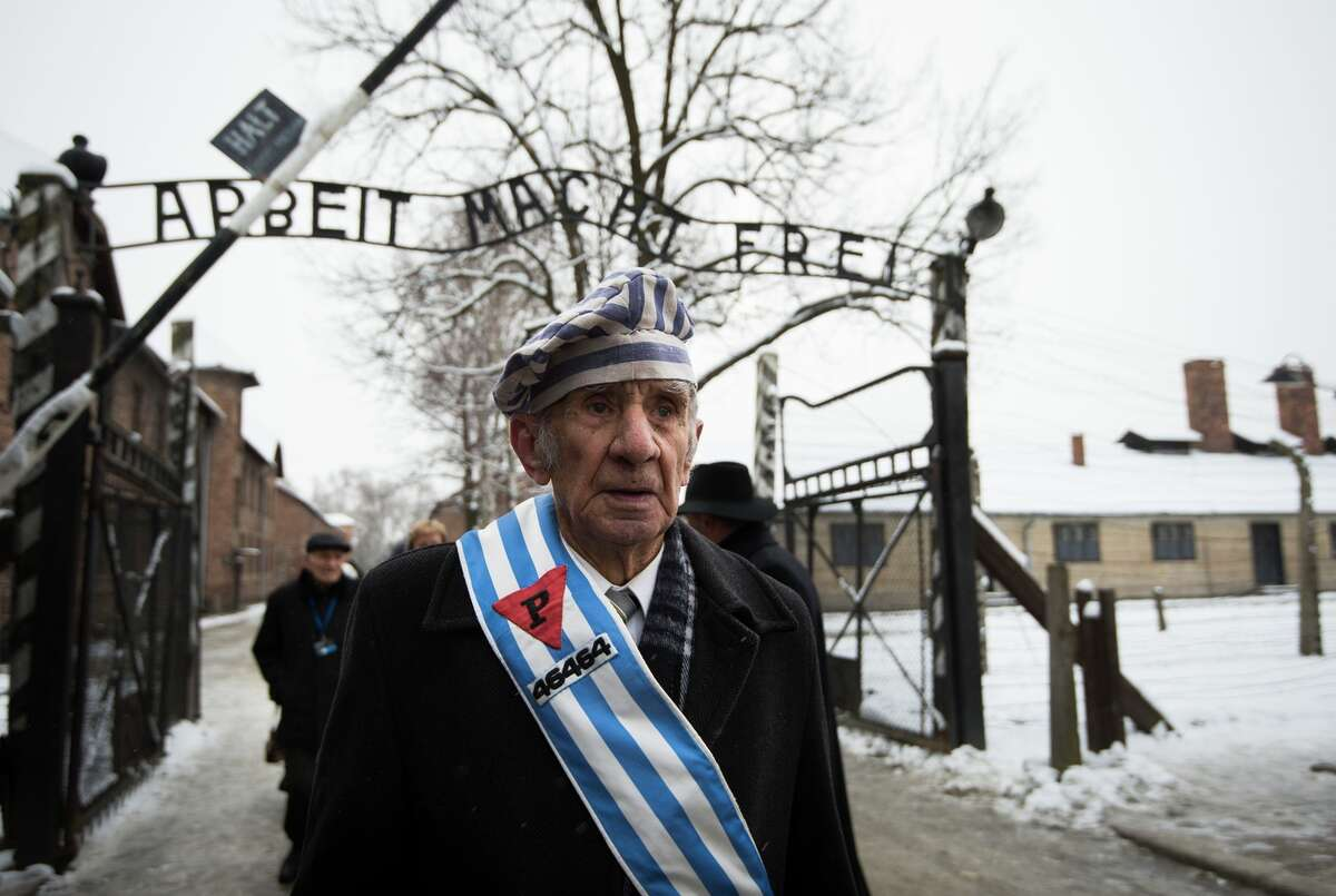 """Survivor Miroslaw Celka walks out the gate with the sign saying """"Work makes you free"""" after paying tribute to fallen comrades at the former concentration camp in Oswiecim, Poland."""