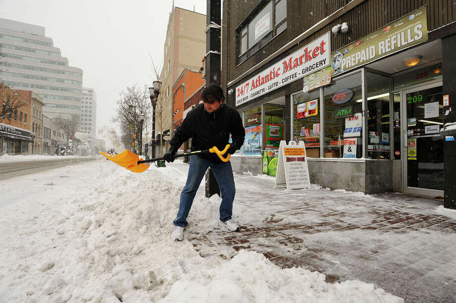Owner of 24/7 Atlantic Market Sanjay Patel shovels in front of his business in downtown Stamford, Conn., during the snow storm that hit New England on Tuesday, Jan. 27, 2015. He said he expects business to pick back up around 6 p.m. Photo: Jason Rearick / Stamford Advocate