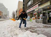 Owner of 24/7 Atlantic Market Sanjay Patel shovels in front of his business in downtown Stamford, Conn., during the snow storm that hit New England on Tuesday, Jan. 27, 2015. He said he expects business to pick back up around 6 p.m.