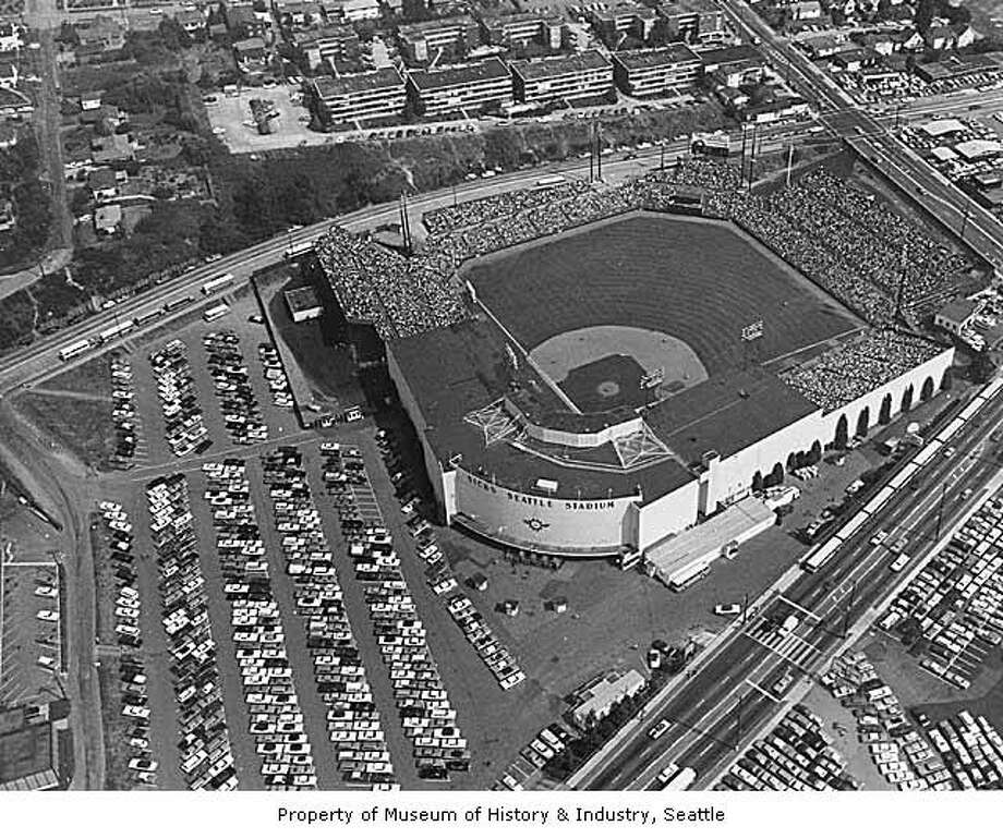 Sick's Stadium: Businessman Emil Sick bought the Seattle Indians baseball team in 1937 and renamed it the Seattle Rainiers. He also started work on a new steel and concrete baseball stadium in Rainier Valley, south of downtown. Sick's Seattle Stadium opened in June 1938. For years, fans crowded the stadium or watched from the slopes overlooking the outfield. By the 1960s, fewer people were going to the games, but the stadium was home to the Seattle Pilots in 1969, before they were moved to Milwaukee. The stadium was torn down in the 1970s. This photo shows Rainier Avenue South in the foreground and South McClelland Street in the upper right. Photo: PI