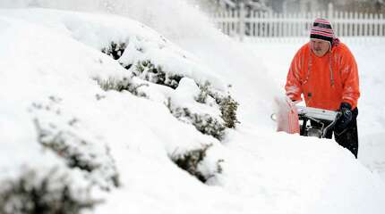 David Stec starts cleaning up the snow around his home in Derby Tuesday, Jan. 27, 2015 during the winter storm that hit the region.