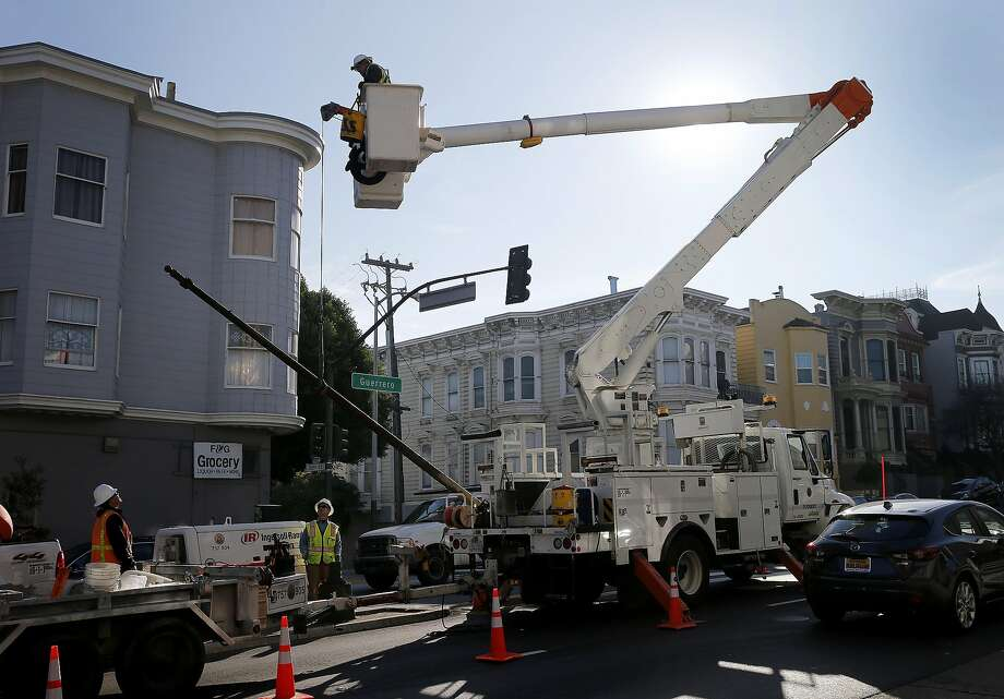 Streetlight crews removed one of the old steel poles that will be replaced with aluminum and a new LED light Wednesday January 21, 2015. San Francisco, Calif. is beginning to change its street lights from high pressure sodium to LED's, and also changing some old steel light poles with new aluminum versions. Photo: Brant Ward, The Chronicle