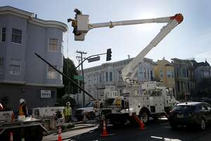 Streetlight crews removed one of the old steel poles that will be replaced with aluminum and a new LED light Wednesday January 21, 2015. San Francisco, Calif. is beginning to change its street lights from high pressure sodium to LED's, and also changing some old steel light poles with new aluminum versions.