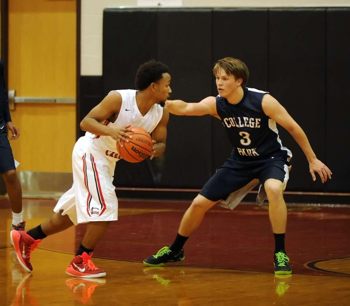 Woodlands College Park visited Langham Creek High School for a basketball game. 11-17-2014. College Park won the game, 59-54. Right, College Park's Chandler Morris (3) applied defensive pressure on Langham Creek's D'Von England (4).