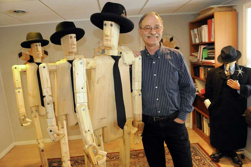 Artist Peter Leue stands with three of his wooden posers, which are life-sized, flexible and pose-able sculptures, on Tuesday, Jan. 27, 2015, at his home in Albany, N.Y. (Cindy Schultz / Times Union)