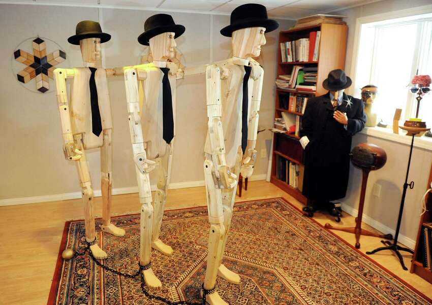 Three of Peter Leue's wooden posers form a chain gang wooden on Tuesday, Jan. 27, 2015, at his home in Albany, N.Y. Posers are life-sized, flexible and pose-able sculptures.(Cindy Schultz / Times Union)