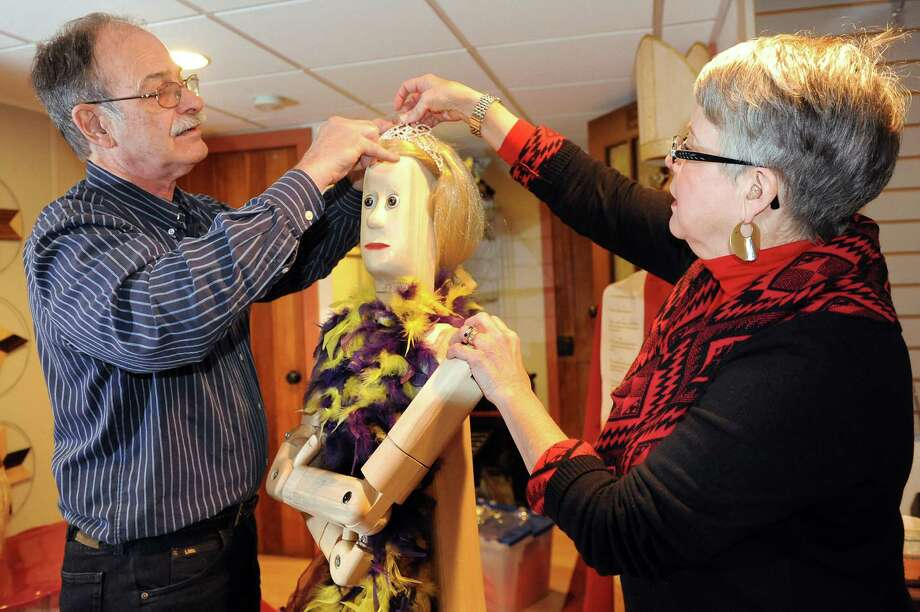 Artist Peter Leue, left, and his wife, Nancy Burton, put the finishing touches on a female wooden poser with a Mardi Gras theme on Tuesday, Jan. 27, 2015, at their home in Albany, N.Y. Posers are life-sized, flexible and pose-able sculptures.(Cindy Schultz / Times Union) Photo: Cindy Schultz / 00030326A