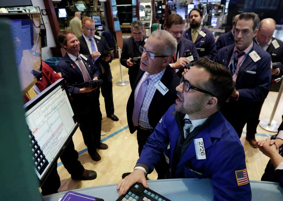 Specialist Paul Cosentino, foreground center, works at the post that handles Cliffs Natural Resources, on the floor of the New York Stock Exchange Tuesday, Jan. 27, 2015. U.S. stocks are tumbling in midday trading, weighed down by disappointing forecasts from big-name companies and an unexpected drop in orders of long-lasting goods. (AP Photo/Richard Drew) Photo: Richard Drew, STF / AP