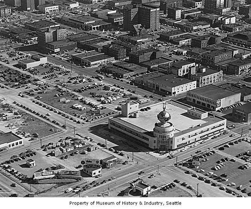 Aerial looking southwest showing Post-Intelligencer building Seattle, 1953 - MOHAI caption: The Seattle Post-Intelligencer started publishing in 1881. In the late 1940s, the newspaper held a nationwide competition for an architect for a new building on Wall Street. The design included a large, revolving globe with an eagle on top, which stood above the entryway. The streamlined style of the building, with its glass and flat surfaces, was very popular during the 1930s and 1940s.