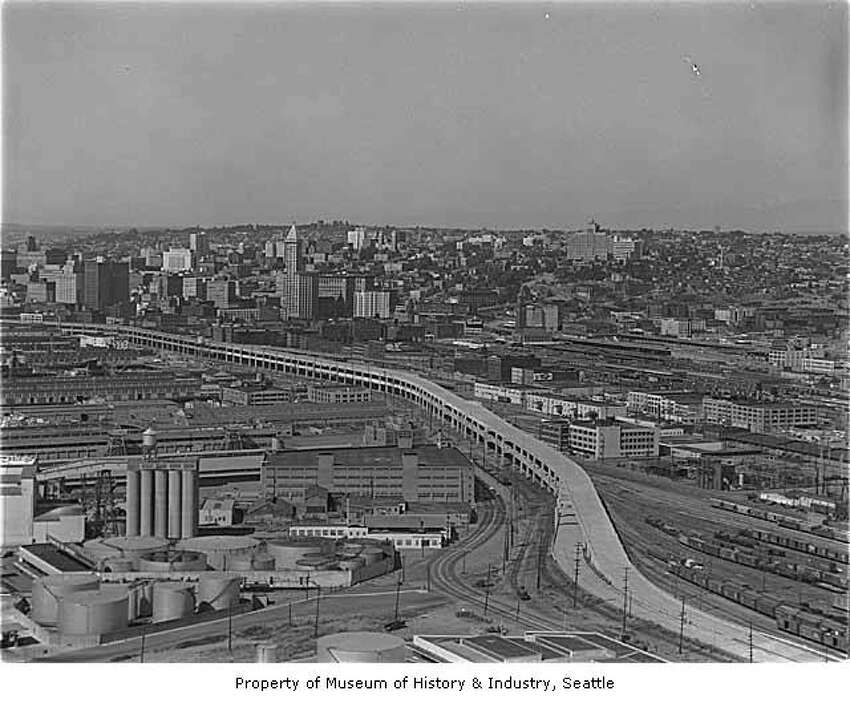 Aerial of Alaskan Way Viaduct extension south to Spokane Street with a view northeast toward Seattle, 1959 - MOHAI caption: Seattle's Alaskan Way Viaduct carries traffic over the waterfront area, linking the northern part of the city to the industrial area south of the central business district. The first unit of the elevated roadway, from Battery Street to Dearborn Street, was completed in 1953 and a southern extension in 1959 .