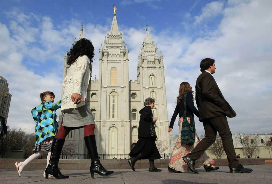 """FILE - In this April 5, 2014 file photo, people walk past the Salt Lake Temple in Salt Lake City. On Tuesday, Jan. 27, 2015, Mormon leaders made a national appeal for what they called a """"balanced approach"""" in the clash between gay rights and religious freedom, promising to support some housing and job protections for gays if they back some exemptions for religious objectors to same-sex marriage. (AP Photo/Rick Bowmer) Photo: Rick Bowmer, STF / AP"""