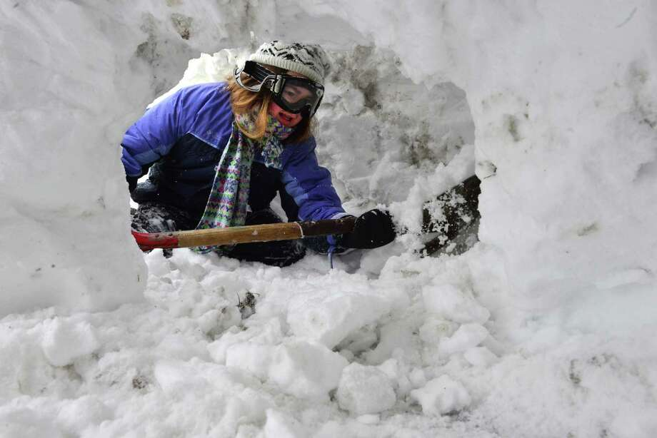 Jacquline Young digs a snow cave in her grandfather's driveway, Tuesday, Jan. 27, 2015, in Easthampton, Mass. A blizzard slammed New England on Tuesday, piling up more than two feet of snow. Photo: John Suchocki, Associated Press / The Republican
