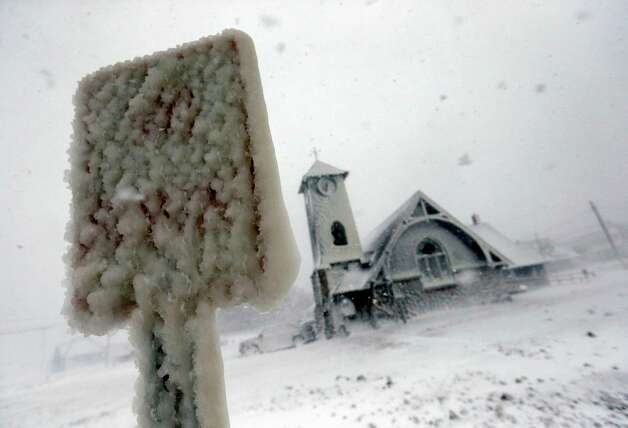 Frozen sea spray coats a road sign and a church during a winter storm in Marshfield, Mass., Tuesday, Jan. 27, 2015. The storm punched out a section of the seawall in the coastal town, police said. (AP Photo/Michael Dwyer) ORG XMIT: MAMD125 Photo: Michael Dwyer / AP