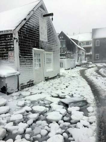 This image provided by Greg Hinson shows icy water covering a street in Nantucket, Mass., Tuesday, Jan. 27, 2015. In New England, the storm that arrived Monday evening was a bitter, paralyzing blast. At least 2 feet of snow was expected in most of Massachusetts, potentially making it one of the top snowstorms of all time there. (AP Photo/NantucketStock.com, Greg Hinson) ORG XMIT: NY124 Photo: Greg Hinson / NantucketStock.com