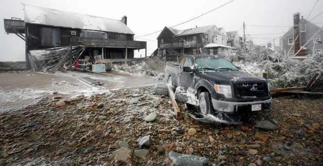 Damaged houses and a truck sit along the coast in the Brant Rock section of Marshfield, Mass., during a winter snowstorm Tuesday, Jan. 27, 2015. Two feet of snow or more was expected in most of Massachusetts by the end of the storm. (AP Photo/The Patriot Ledger, Greg Derr) BOSTON GLOBE OUT. BOSTON HERALD OUT. ORG XMIT: MAQUI102 Photo: Greg Derr / AP