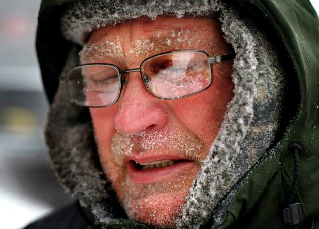 Snow clings to the face of man as he braces himself against a gust of wind while shoveling a sidewalk, Tuesday, Jan 27, 2015, in downtown Portland, Maine.  Forecasters with the National Weather Service in Gray have said that much of southern Maine will see 12 to 18 inches of snow, while small bands of intense snowfall will increase those totals in localized areas. (AP Photo/Robert F. Bukaty) ORG XMIT: MERB102 Photo: Robert F. Bukaty / AP