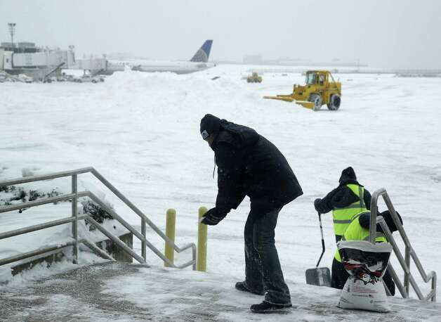 Men and machines clear snow off the tarmac at LaGuardia Airport in New York, Tuesday, Jan. 27, 2015. A storm packing blizzard conditions spun up the East Coast early Tuesday, pounding parts of coastal New Jersey northward through Maine with high winds and heavy snow. (AP Photo/Seth Wenig) ORG XMIT: NYSW122 Photo: Seth Wenig / AP
