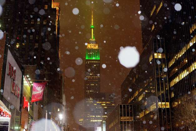 Snow falls around the Empire State Building in midtown Manhattan, on Monday, Jan. 26, 2015, in New York. Tens of millions of people along the Philadelphia-to-Boston corridor rushed to get home and settle in Monday as a fearsome storm swirled in with the potential for hurricane-force winds and 1 to 3 feet of snow that could paralyze the Northeast for days. (AP Photo/Patrick Sison) ORG XMIT: NYPS101 Photo: Patrick Sison / AP