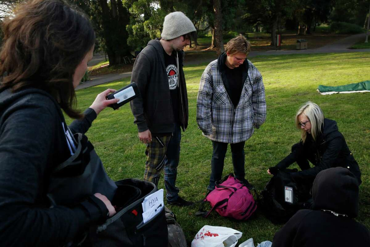 Senior Outreach Counselor Jennifer Cowles (left) and Mary Howe (far right), executive director of the Homeless Youth Alliance, Mary Howe, give out supplies and chat with Valentine, 20 (left), and Tyi, 24, during an outreach session in GoldenGate Park near Haight Street. The alliance lost its lease on its drop-in center on Christmas 2013, and now work out of a garage and the home of a doctor in trhe neighborhood.