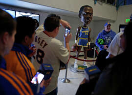Fans crowd around an 8-foot, 4-inch bobble head statue of former Warrior Manute Bol, who actually stood 7-foot-7.
