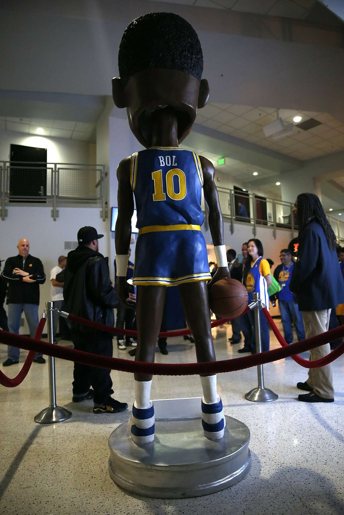 """Golden State Warriors' fans crowd around an 8' 4"""" Manute Bol bobble head at Oracle Arena in Oakland, Calif., on Tuesday, January 27, 2015."""