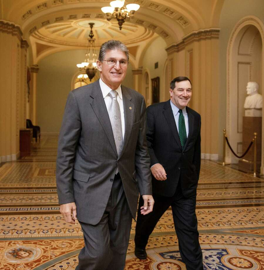Sen. Joe Manchin, D-W.Va., left, the Democratic co-sponsor of the Keystone XL pipeline bill, walks with Sen. Joe Donnelly, D-Ind., as the vote to cut off debate on the long-stalled  legislation fell short, at the Capitol in Washington, Monday, Jan. 26, 2015. The pipeline would carry oil from Canada to refineries on the Gulf Coast but has been opposed by environmental groups and President Obama has threatened to veto the bill if passed. (AP Photo/J. Scott Applewhite) Photo: J. Scott Applewhite, STF / AP