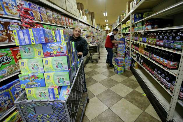 Jonathan Herrera, left, and Jaime Raymondo restock the shelves at the Islip Food Warehouse, Tuesday, Jan. 27, 2015 in Central Islip, N.Y.  A storm packing blizzard conditions spun up the East Coast early Tuesday, pounding coastal eastern Long Island into Maine with high winds and heavy snow. (AP Photo/Mary Altaffer) ORG XMIT: NYMA116 Photo: Mary Altaffer / AP