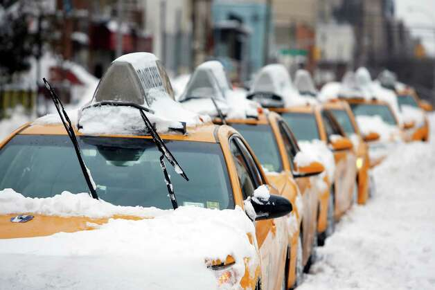 Taxis that belong to Arthur Cab Leasing Corp.,  stand idle outside the company's lot before being put it back into service following a winter storm, Tuesday, Jan. 27, 2015, in the Queens borough of New York.  Manager Shaon Chowdhury estimates that the winter storm has cost his company approximately $60,000 in lost revenue and added expenses. (AP Photo/Jason DeCrow) ORG XMIT: NYJD113 Photo: Jason DeCrow / FR103966 AP