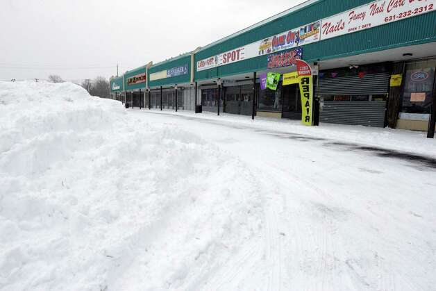 Stores are closed at a Central Islip, N.Y. strip mall, Tuesday, Jan. 27, 2015.  A storm packing blizzard conditions spun up the East Coast early Tuesday, pounding coastal eastern Long Island into Maine with high winds and heavy snow. (AP Photo/Mary Altaffer) ORG XMIT: NYMA113 Photo: Mary Altaffer / AP