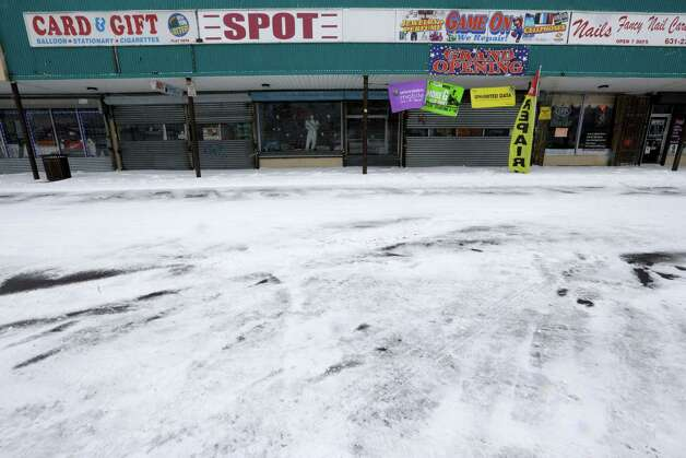 Stores are closed at a Central Islip, N.Y. strip mall, Tuesday, Jan. 27, 2015.  A storm packing blizzard conditions spun up the East Coast early Tuesday, pounding coastal eastern Long Island into Maine with high winds and heavy snow. (AP Photo/Mary Altaffer) ORG XMIT: NYMA114 Photo: Mary Altaffer / AP