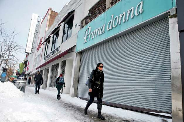 Pedestrians walk past closed businesses along Steinway Street, normally a busy commercial area, following a winter storm, Tuesday, Jan. 27, 2015, in the Queens borough of New York. Economists are split on the cost of the decision to essentially shut down the city with a sweeping lockdown of all buses, commuter trains, buses, and a ban of any kind of travel on bridges, tunnels and roads from highways to neighborhood streets. But residents say they felt it in lost wages and unnecessary days off work. (AP Photo/Jason DeCrow) ORG XMIT: NYJD114 Photo: Jason DeCrow / FR103966 AP