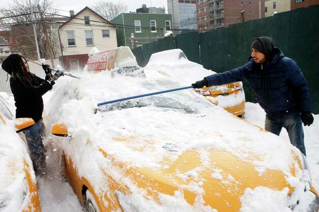 Shaon Chowdhury, right, manager of Arthur Cab Leasing Corp., and employee Kyle Hinkson, of Harlem, clear snow from a taxi while preparing to put it back into service following a winter storm, Tuesday, Jan. 27, 2015, in the Queens borough of New York. Chowdhury estimates that the winter storm has cost his company approximately $60,000 in lost revenue and added expenses. (AP Photo/Jason DeCrow) ORG XMIT: NYJD112 Photo: Jason DeCrow / FR103966 AP