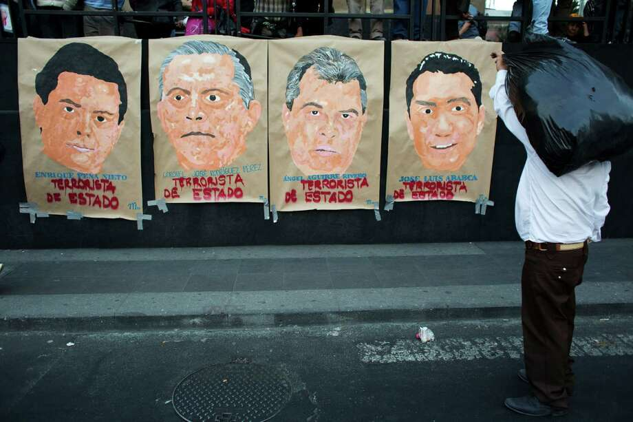 "A passerby carrying stops to look at posters depicting politicians including President Enrique Pena Nieto, left, along with the words in Spanish ""State terrorist.""  Photo: Rebecca Blackwell, STF / AP"