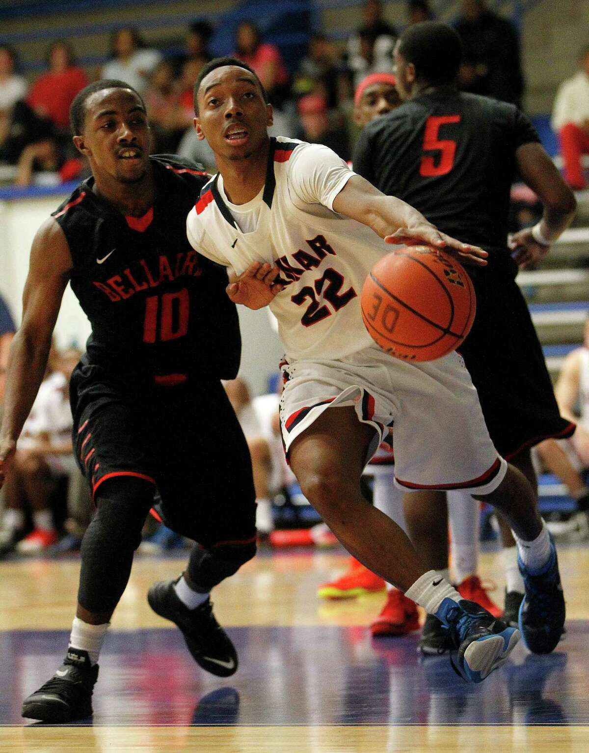 Lamar's Darrion Butler (22) reaches for a loose ball with Bellaire's Jarren Greenwood (10) during the first half of the Bellaire-Lamar High School boys basketball game at the Pavillion, Tuesday, Jan. 27, 2015, in Houston.