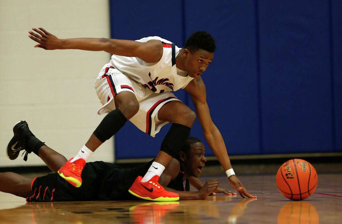 Lamar's Rodrick Harris (24) reaches for a loose ball with Bellaire's Maxwell Evans (1) during the first half of the Bellaire-Lamar High School boys basketball game at the Pavillion, Tuesday, Jan. 27, 2015, in Houston.