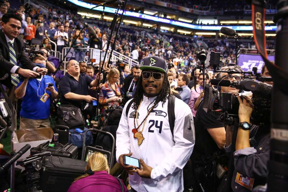 Marshawn Lynch wades through members of the media to his podium during Super Bowl XLIX Media Day on Tuesday, January 27, 2015, at the US Airways Center in Phoenix, Arizona.