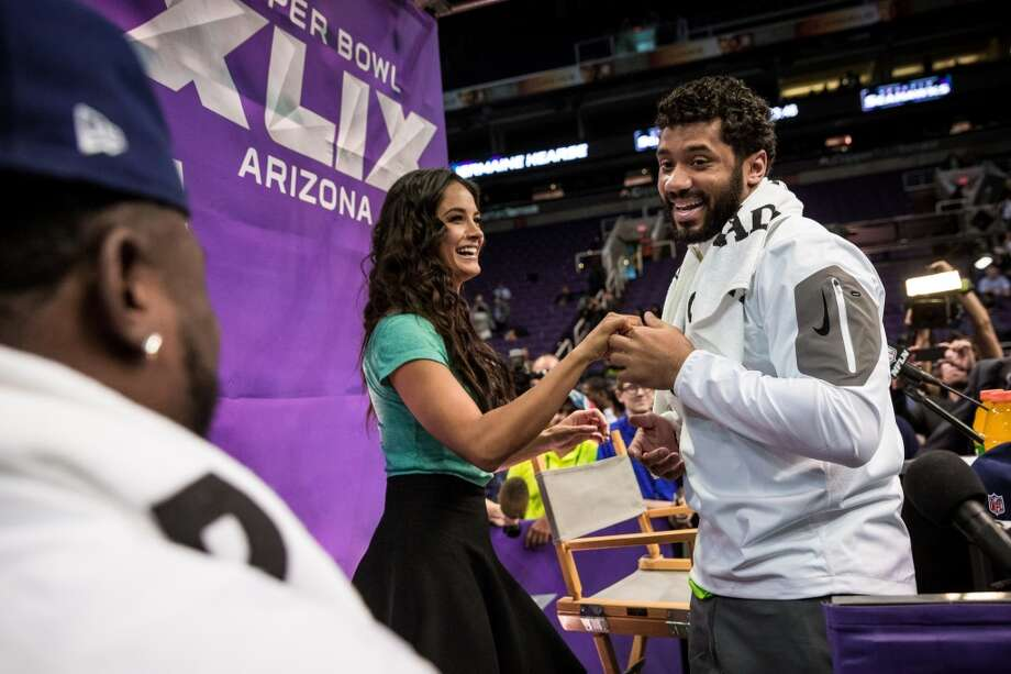 Christine Michael, left, forces Seahawks quarterback Russell Wilson, right, to dance with Televisa host Gina Holguin, center, during Super Bowl XLIX Media Day Tuesday, January 27, 2015, at the US Airways Center in Phoenix, Arizona. Photo: JORDAN STEAD, SEATTLEPI.COM