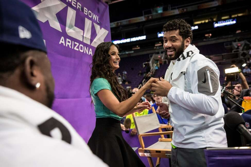 Christine Michael, left, forces Seahawks quarterback Russell Wilson, right, to dance with Televisa host Gina Holguin, center, during Super Bowl XLIX Media Day Tuesday, January 27, 2015, at the US Airways Center in Phoenix, Arizona.