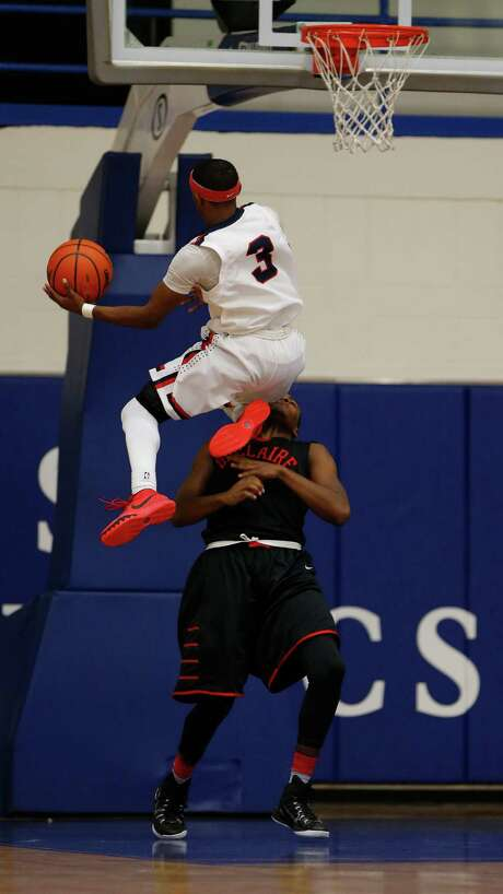 Lamar's Markus Vallien shows off his leaping ability by going over Bellaire's Alexander Duke. Photo: Karen Warren, Staff / © 2015 Houston Chronicle
