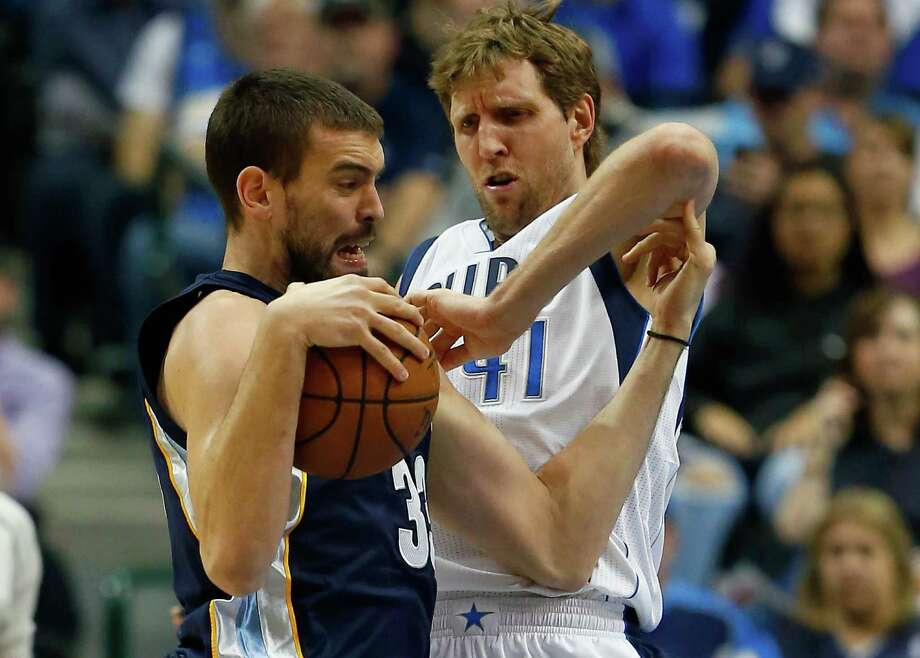 The Mavs' Dirk Nowitzki, right, gets physical in an attempt to stop a drive by the Grizzlies' Marc Gasol. Photo: Tom Pennington, Staff / 2015 Getty Images