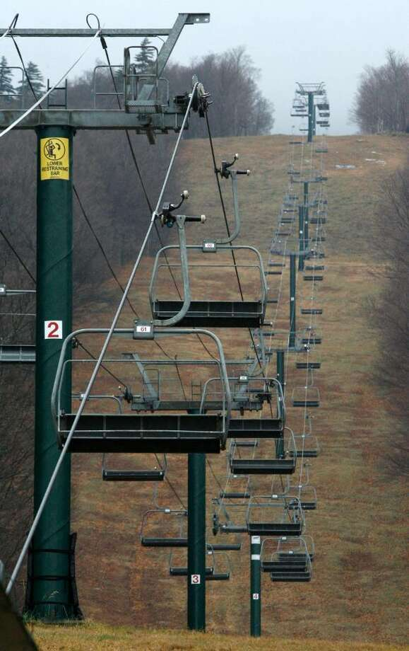 Ski lifts are silent and the slopes are bare at the Sugarbush ski resort in Warren, Vt., Friday, Nov. 27, 2009. Many Vermont ski areas have been closed for the Thanksgiving holiday.  Weather forecasters say a strong nor'easter storm is heading through New England on Friday, with the possibility of leaving behind some high-elevation snow for Vermont's ski slopes.(AP Photo/Toby Talbot) Photo: Toby Talbot, AP / AP2009