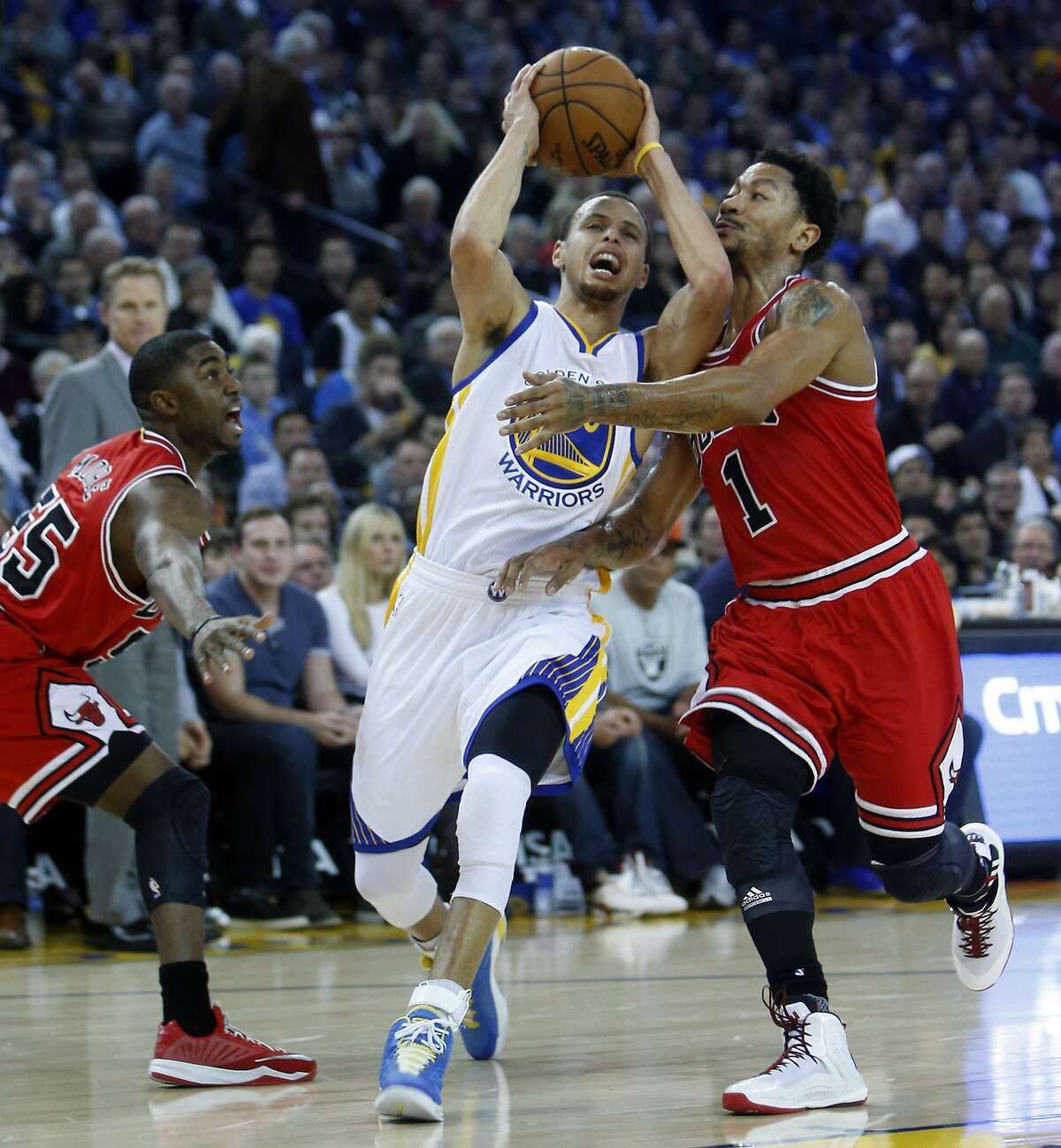 The Golden State Warriors' Stephen Curry drives against the defense of Chicago Bulls' Derrick Rose and E'Twaun Moore in 1st quarter during NBA game at Oracle Arena in Oakland, Calif., on Tuesday, January 27, 2015.