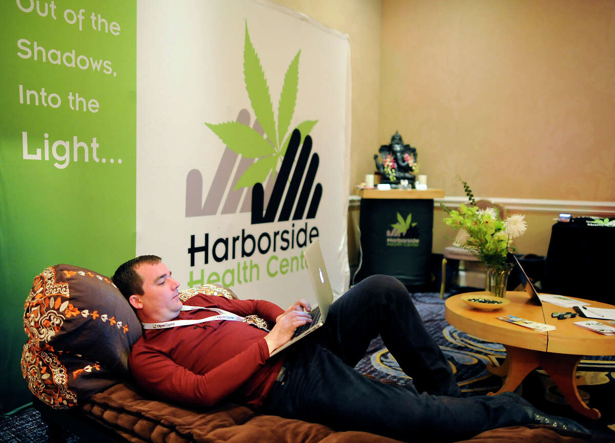 Aaron Smith, executive director of the National Cannabis Industry Association, relaxes in the Harborside Health Center booth at the ArcView Group's high-worth pot investors' conference in San Francisco.
