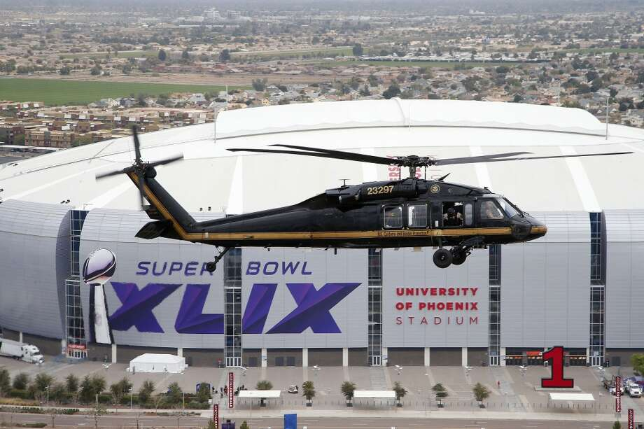 A U.S. Customs and Border Protection Black Hawk helicopter flies above University of Phoenix Stadium, site of Super Bowl XLIX football game, during a security demonstration for the media Monday, Jan. 26, 2015, in Glendale, Ariz. The helicopters and truck-sized X-ray machines that are typically deployed along the U.S.-Mexico border have been brought to the Super Bowl venue to assist with the security effort. (AP Photo/Ross D. Franklin) Photo: Associated Press