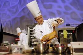 "Philip Tessier, of USA, prepares food during the ""Bocuse d'Or"" (Golden Bocuse) trophy, at the 15th World Cuisine contest, in Lyon, central France, Tuesday, Jan. 27, 2015. The contest, a sort of world cup of the cuisine, was started in 1987 by Lyon chef Paul Bocuse to reward young international culinary talents. (AP Photo/Laurent Cipriani)"