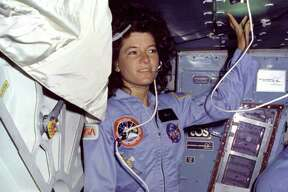 On Challenger's middeck, Mission Specialist (MS) Sally Ride, wearing light blue flight coveralls and communications headset, floats alongside the middeck airlock hatch.