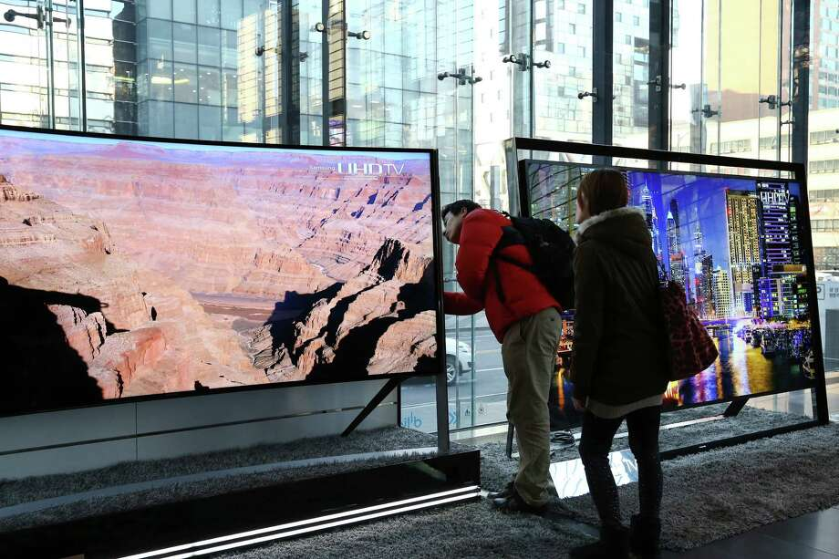 Visitors inspect a Samsung Electronics Co. curved ultra high definition (UHD) television at the company's d'light showroom in Seoul, South Korea, on Tuesday, Jan. 27, 2015. Samsung, the world's largest producer of smartphones using Google Inc.'s Android, is scheduled to release fourth-quarter earnings results on Jan. 29. Photographer: SeongJoon Cho/Bloomberg Photo: SeongJoon Cho / Bloomberg / © 2015 Bloomberg Finance LP