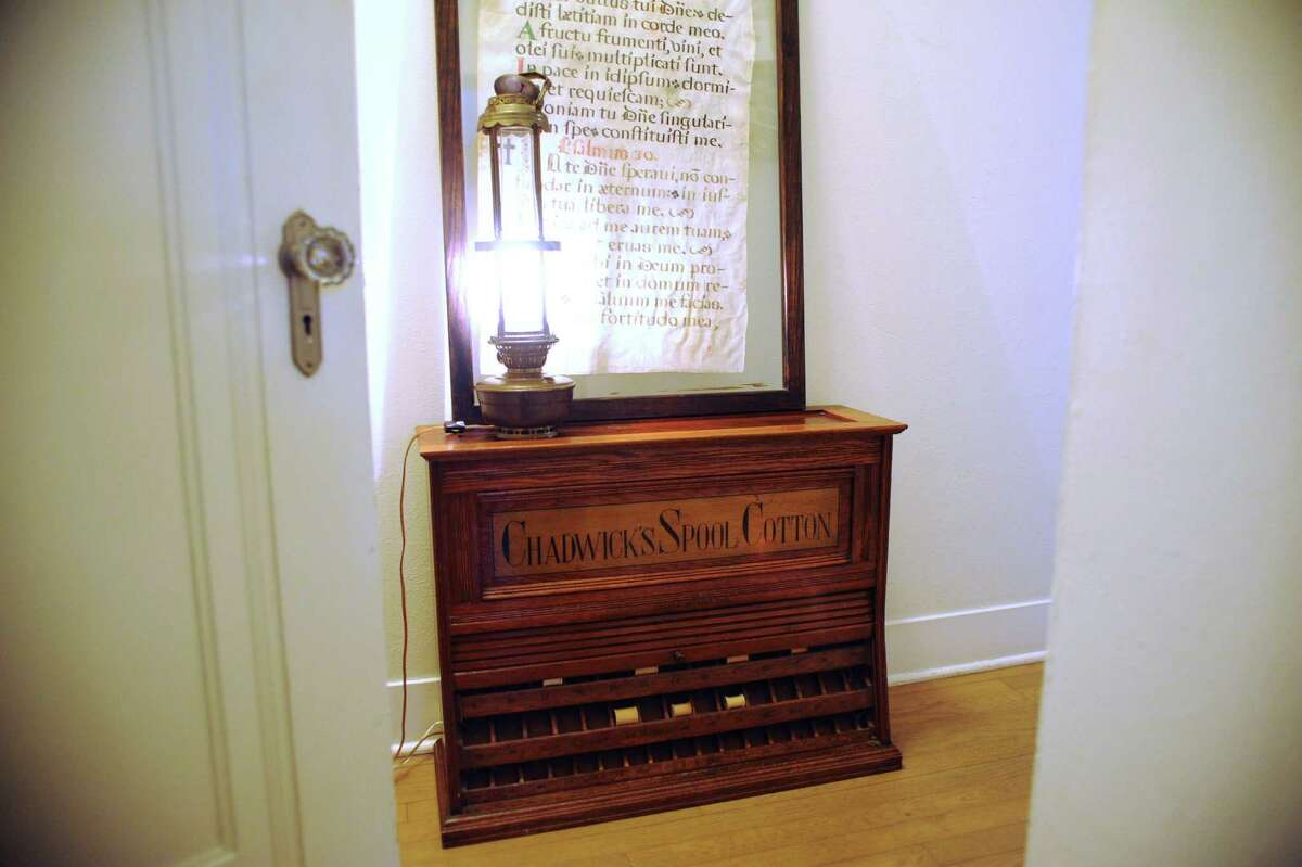 A thread case is among the furnishings Jean has incorporated from her grandfather's store in Moulton. On it, she displays a framed piece of antique vellum from a Spanish church.