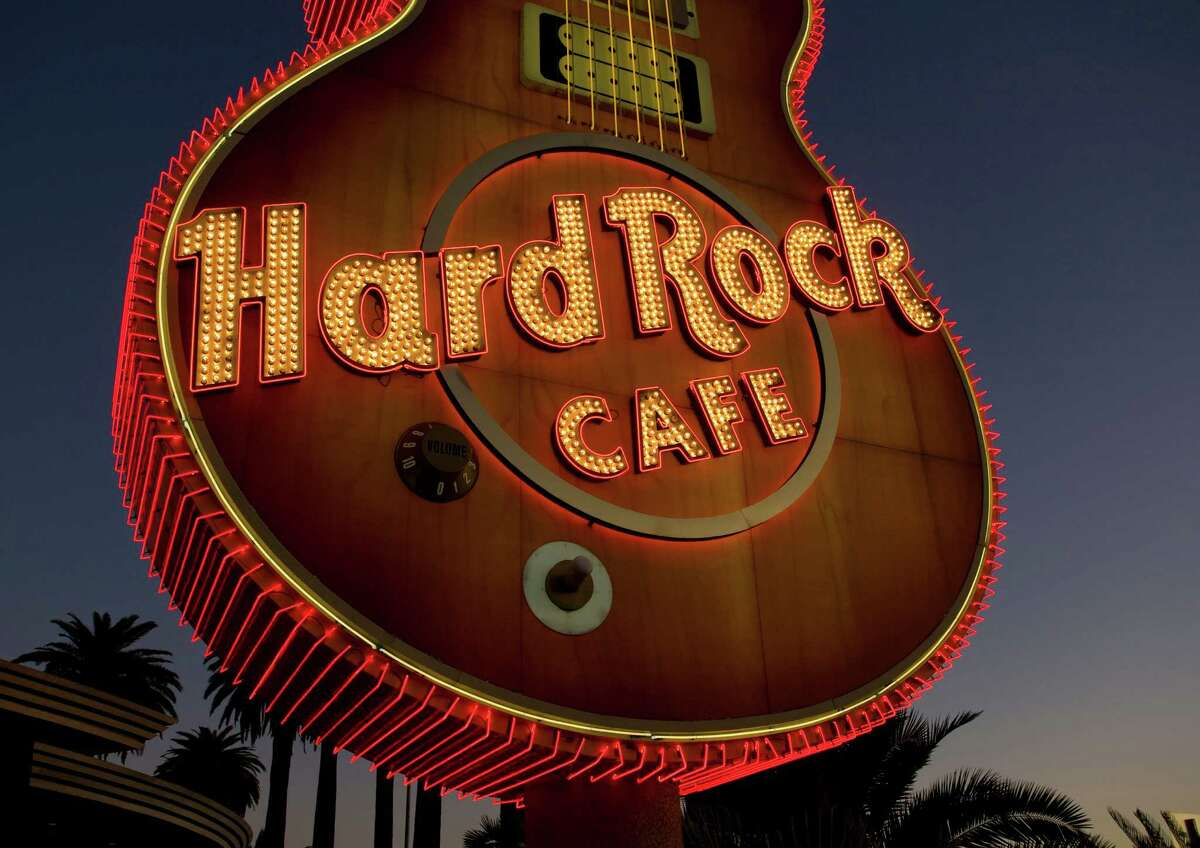 LAS VEGAS, NV - OCTOBER 23: The Hard Rock Cafe neon sign, located on East Harmon Avenue, is viewed at sunrise on October 23, 2011 in Las Vegas, Nevada. Though tourism is slowly making a comeback on the Strip, the economic conditions just two blocks away remain mired in poverty and desolation.